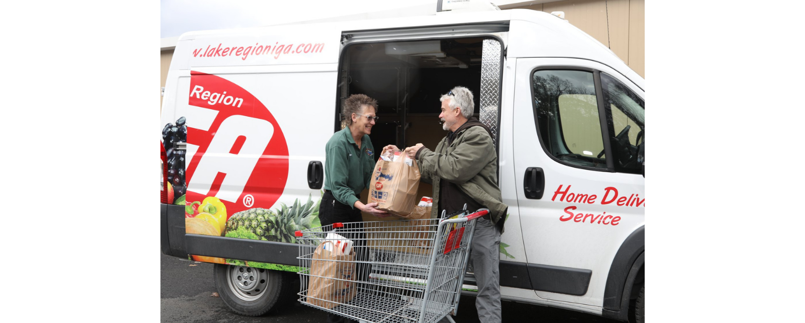 A man and a woman loading groceries into a Lake Region IGA delivery van